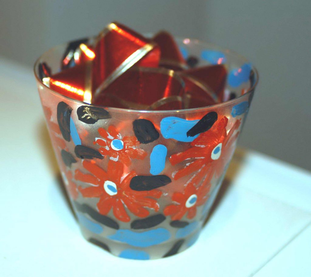 Painted plastic cup with red ribbon