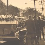 Hearse with flowers and pall bearers